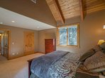 The vaulted wood-beamed ceilings create a cozy space to drift off to sleep in the Guest Bedroom 2.