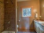 The main level Guest Bathroom 3 has a warm, clean design with a shower/tub combo.