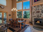 The natural wood beams and stone fireplace perfectly complement the rustic wood scenery beyond the windows.