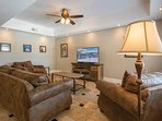 The lower level living room features a flat screen TV and comfy sofas for relaxing.