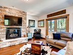 The main level living area has a flatscreen TV, gas fireplace, leather sectional, and views of the ski mountain.