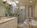 Master Bathroom #1 has a private bath with double vanity, glass shower, soaking tub, and artistic tile work.
