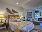Guest Bedroom #2 on the second floor has a Queen bed with rattan headboard, an extra seating area, and a private bath.