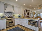 The spacious kitchen has granite countertops, stainless appliances like a professional range with hood, plenty of...