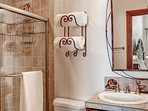 Spruce up in the en-suite bathroom with a walk-in shower and single sink vanity.