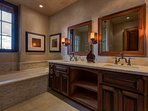 The master en suite has dual sinks, a shower, and relaxing soaking tub.