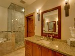 Luxury private bathroom to Master Bedroom #1 with a jetted tub, steam shower, heated floors, and natural stone