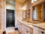 The opulent private bathroom to this master has granite counters, dual sinks, and an elegantly tiled shower/tub combo.