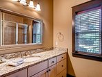 This master's en suite has a shower/tub combo and a single vanity with a beautiful countertop and under-mount sink.