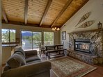 The great room features an open layout, hardwood floors, a stone fireplace, lake views, and access to a balcony.