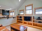The above garage living space has a living area with sleeper sofa and flatscreen TV.