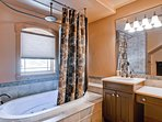 The private bath for master bedroom #2 includes a jetted tub/rainshower combo.