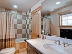 The private bathroom in the above garage living space has a tub/shower combo.