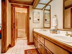 This guest bathroom features a double vanity and a walk-in shower. It's attached to Guest Bedroom #2.