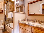 The first floor bathroom is adorned with granite countertops and features a tub/shower combo.