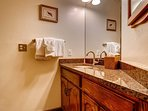 This guest bathroom has a vanity with granite countertops.
