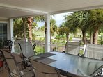 Patio bedroom sliding door, dining set and extra seating group with view west towards golf driving range.
