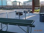 charcoal grills, trash can and water hose, and picnic tables.