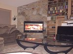 Living room with wood burning fireplace and 43'' roku tv