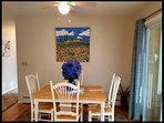 Dining area.  More chairs available.  Highchair also. Artwork is an original.