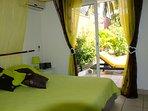 La chambre avec sa baie vitrée donnant sur le jardin et la piscine