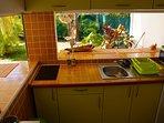 La cuisine avec ses passes plats ouverte sur la terrasse et le jardin.