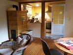 Blick vom Wohnzimmer mit Kachelofen in die Küche
