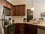 Open concept kitchen with granite counters and stainless steel appliances