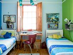 bright and colourful twin room with built in cupboards and air con.