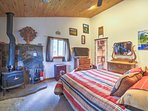 It features a queen bed, wood-burning stove, and a flat-screen Smart TV.