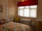 Bedroom 3 with single bed, wardrobe, desk & lamp, hairdryer & vanity unit.