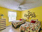 Vibrant walls and 2 twin beds highlight the second bedroom.