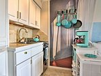 Colorful pots and pans accent this adorable well-equipped kitchen.
