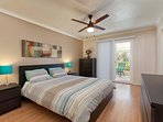 Master bedroom with queen size bed, TV and sliding patio door