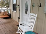The screened porch has two rockers, a swing, and storage for beach chairs.