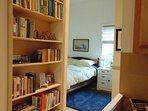 View of sleeping area/bedroom, bookshelves with lots of interesting books to browse.