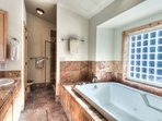 Ensuite bathroom includes plenty of counter and drawer space around sink, walk-in shower, and large bathtub