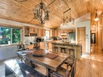 Intricate wooden dining room table with two chairs and benches to seat 6+