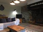 Grand salon avec le charme de la pierre et une belle cheminée