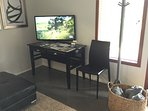 Wall mounted TV over work desk, coat rack and a basket full of blankets for sitting outside