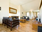spacious lounge with oak floors & contemporary leather sofas