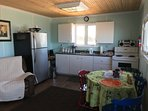 Fully equipped kitchen with full fridge and stove, coffee maker, microwave and cooking spices.