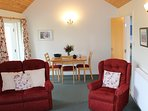 Thairn cottage spacious lounge has comfy seating for 3 and a dining area.