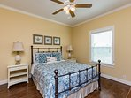 Main level guest bedroom with comfy queen bed and cute coastal décor.