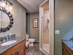 Two sinks and a tiled, glass-enclosed shower detail the master bathroom.