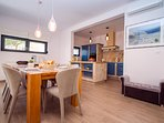 Fully equipped kitchen and dining area with exit to outdoor furniture