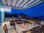 Outdoor dining area in the night with sea and island views