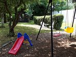 Swings, toddler slide & summerhouse (ball game area is to right of hedge)