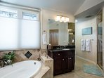 Ensuite -2 vanities, soaking tub, and high end rain shower with towels and toiletry basics provided.