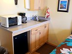 The full kitchenette includes a microwave, small refrigerator, water filter, coffee maker, hot plate (in the cabinet...